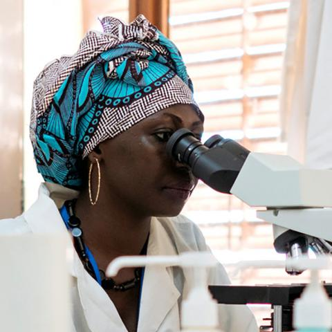 A health worker looks through a microscope in a health facility lab in Mali.